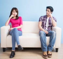 young couple feel bad and look somewhere sit on sofa at home